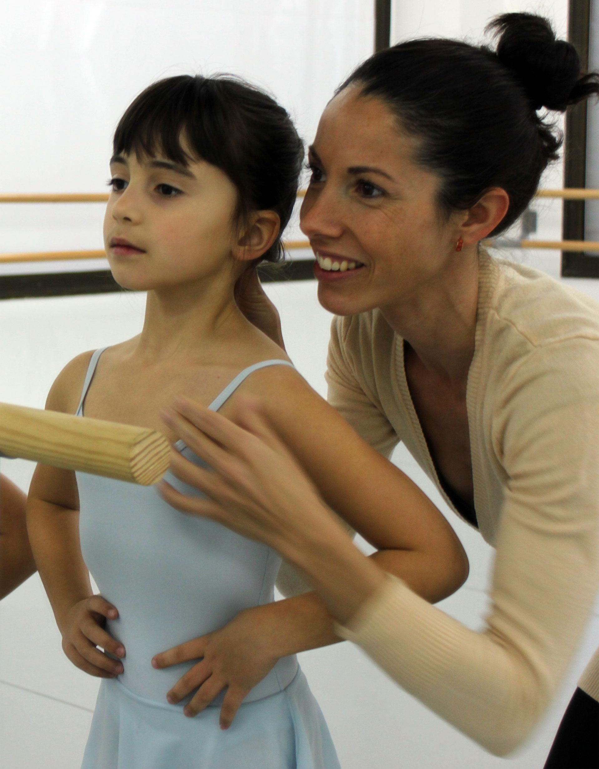 profesora corrigiendo postura de niña de preballet